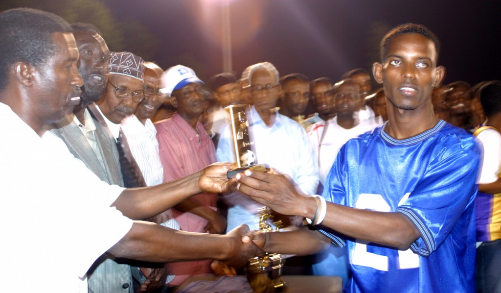 A player from a previous tournament receiving the MVP trophy