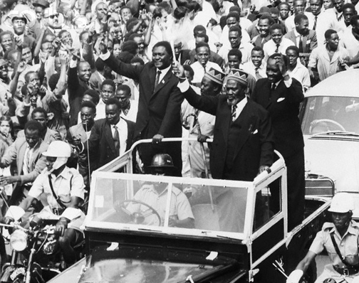 """Nairobi, Kenya – Waving his 'wisk' the newly-elected Premier of Kenya, Jomo Kenyatta (R, foreground), greeted throngs of cheering citizens as he rode through the streets of Nairobi. Accompanying Kenyatta are Tom Mboya (L), Minister of Justice and Constitutional Affairs; A. Oginga Odinga, Minister for Home Affairs; and James S. Gichuru, Minister for Finance. The motorcade was part of the National Holiday celebrations which marked the start of internal self-government for the African nation."" Photo: © Bettmann/CORBIS"