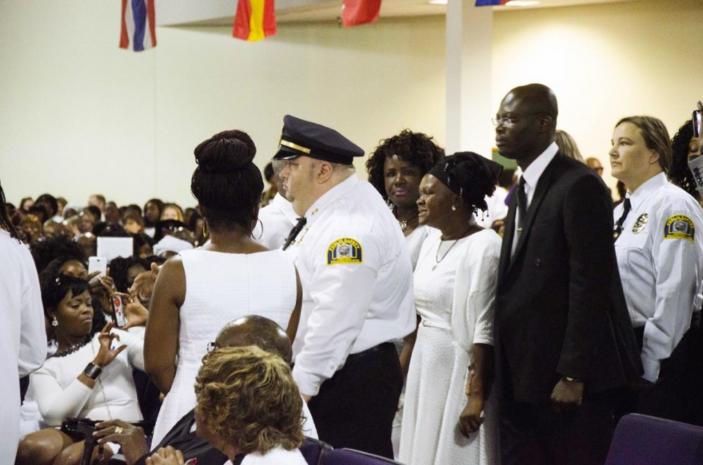Security and family escort Louise Karluah (in black headscarf), the biological mother to the late 10-year-old Barway Collins, into Shiloh Temple International Ministries in Minneapolis on May 2, 2015, for her son's funeral. The funeral was exactly three weeks after his body was found on the Mississippi River on Saturday, April 11. Louise Karluah had just arrived from Liberia three days prior to the funeral Barway's father, Pierre Collins, was taken into custody two days after Barway was found and charged with the murder of his son. Photo: Kaamil Haider/Mshale