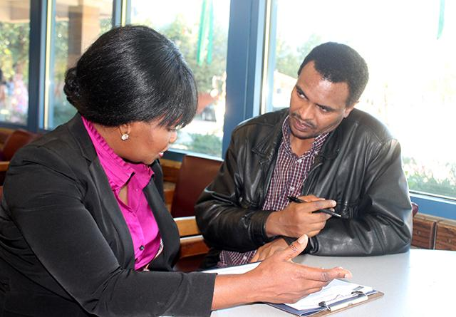 Roseline Shelstad, left, speaking with Zewdu Negash about job training and career opportunities in the Twin Cities. Photo: Ibrahim Hirsi/MinnPost