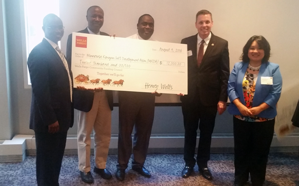 Wells Fargo Minnesota Region president, Joe Ravens (2nd from right) presents a check for $12,000 on Tuesday, August 9, 2016 to Minnesota Kenyan International Development Association (MKIDA) to build a secure website for a youth mentoring program. The grant is through the bank's Community Funding Council which offers onetime funding for eligible organizations. Photo: Tom Gitaa/Mshale